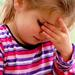 A young girl with her hand on her forehead in frustration