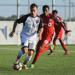 Ryan Williams, with the ball at his feet, running forward with a TFC II player chasing him