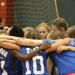 (picture of players in a huddle during a volleyball game)