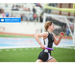 Girls Track runner running with a baton