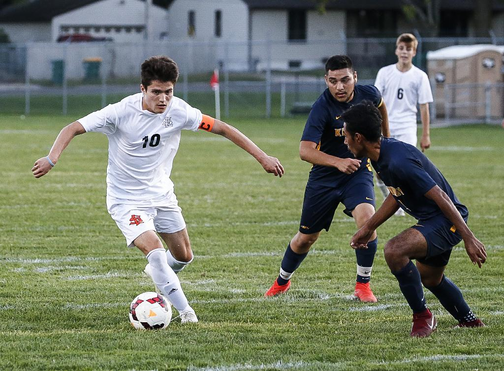St. Louis Park's Nicholas Riley (10) looks to move the ball past a pair of Bloomington Kennedy defenders. Riley scored first for the Orioles in a 2-1 win at Bloomington Stadium. Photo by Cheryl A. Myers, SportsEngine