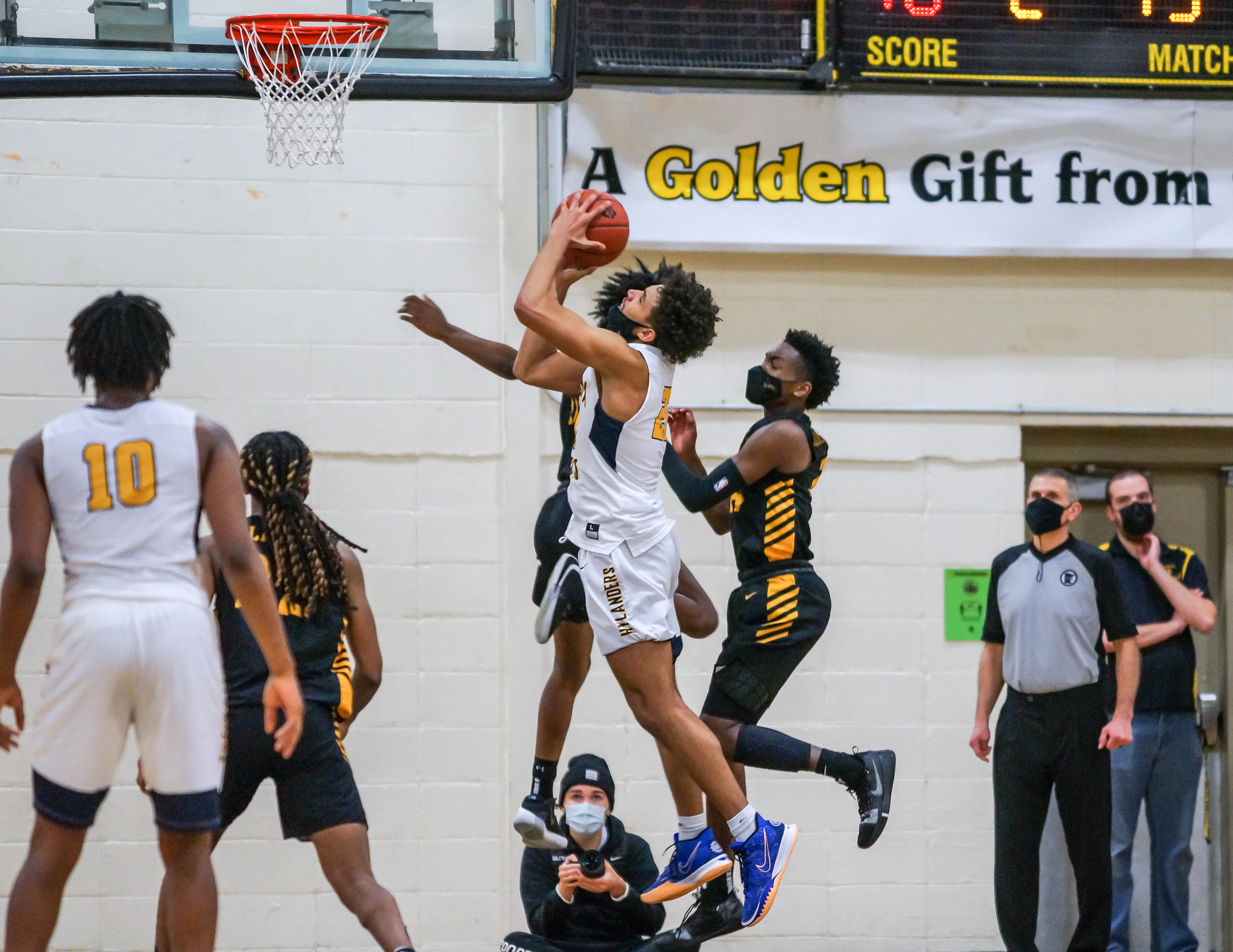 Columbia Heights' Donnavin Hinsz (center) makes the game winning basket while drawing a foul, with less than 5 seconds remaining to give the visiting Hylanders a 62-60 victory over DeLaSalle Feb 23. Photo by Korey McDermott, SportsEngine