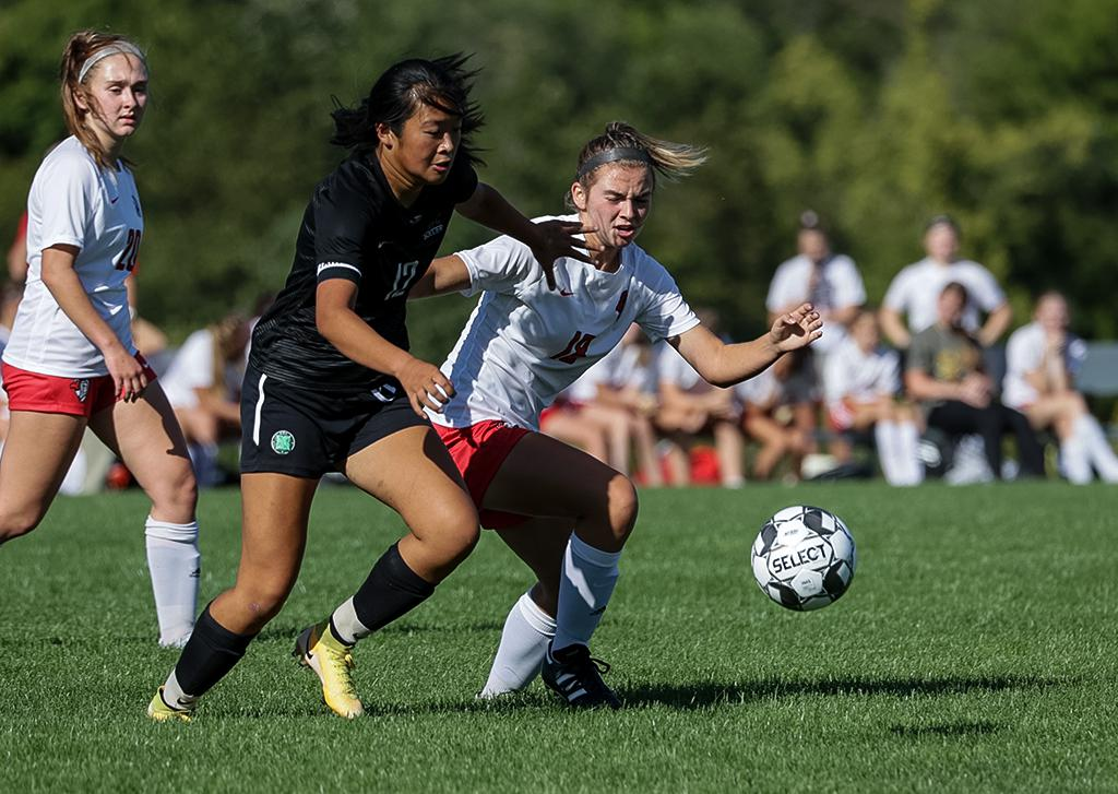 Sophia Anderson (12) and Avery Sames (18) race to the ball at midfield. Sames scored St. Croix Lutheran Academy's only goal on a free kick in the second half. Photo by Cheryl A. Myers, SportsEngine