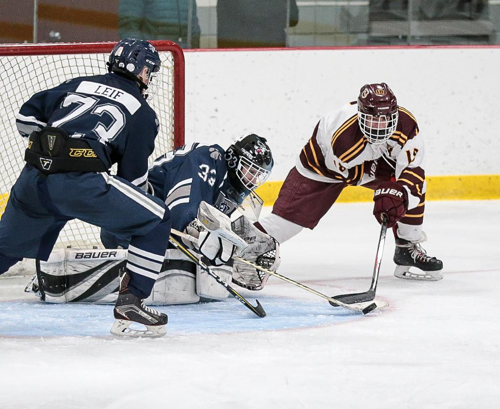 Rochester Century goalie Tim Pundt directs the puck away from South St. Paul's Matt Wincentsen (18) on a wraparound attempt. Pundt tallied 34 saves, leading his team to a 2-2 draw on Saturday. Photo by Cheryl A. Myers, SportsEngine