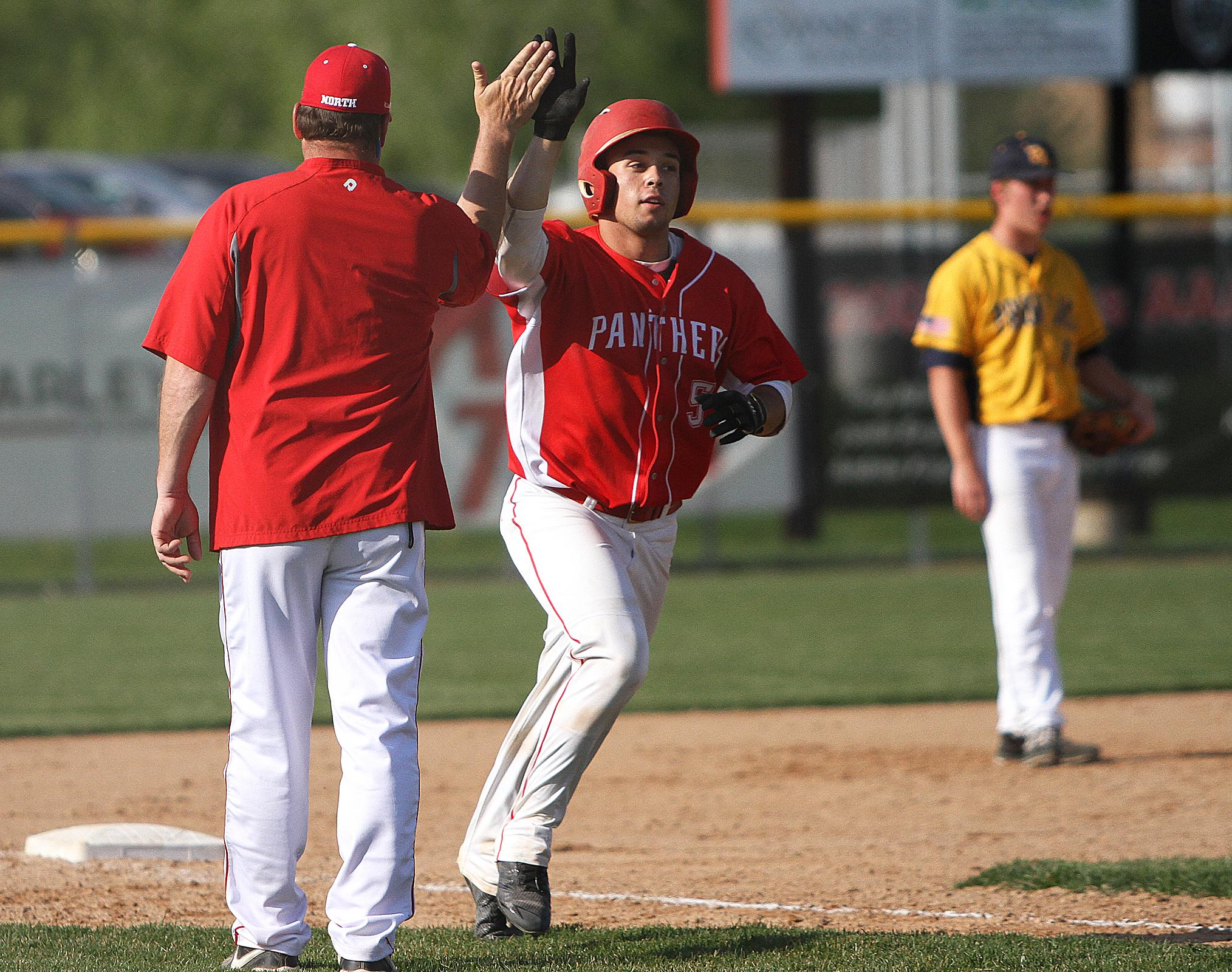 Lakeville North senior Nick Juaire gets a high five as he rounds third after knocking a fifth-inning home run in Wednesday afternoon's 6-3 loss to Prior Lake. Juaire went 2-for-4 with 3 RBI. Photo by Drew Herron, SportsEngine