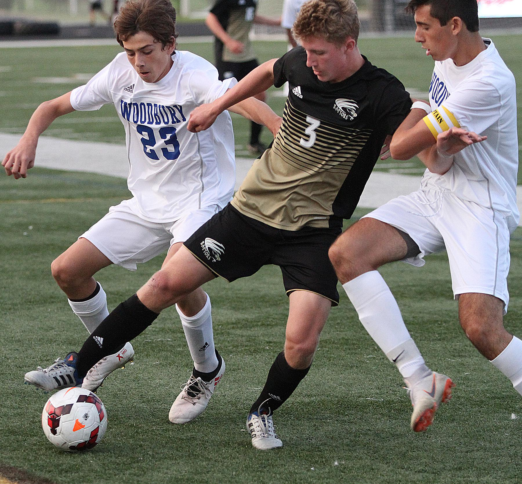 East Ridge junior defender Reese Dodd fights for control of the ball near the sideline with Woodbury's Josh Miller (right) and Devin Padelford in pursuit. Photo by Drew Herron, SportsEngine