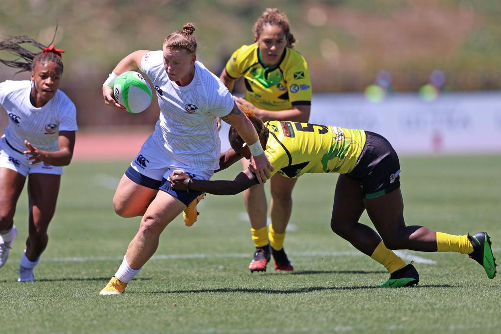 Alev Kelter running with rugby ball being chased by a defender.