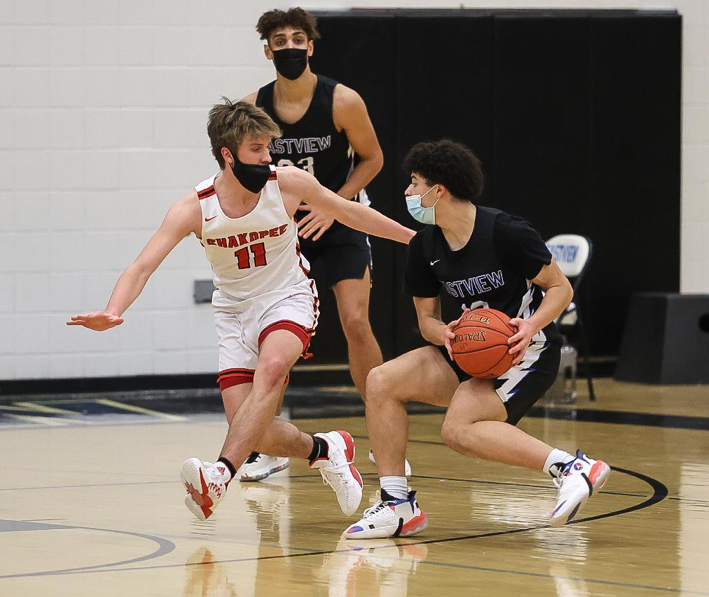 Shakopee's Quinten Snell (11) blocks Kenji Scales' drive to the basket. Snell led the Sabers' scoring with 13 points on Tuesday night. Photo by Cheryl A. Myers, SportsEngine