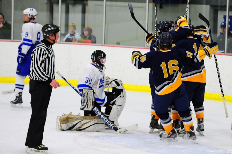 Hermantown defenseman Jared Kolquist (No. 16) celebrates with his teammates as Hopkins goalie Josh Kuemichael (No. 30) watches on Friday, Dec. 9 at the Hopkins Pavillion Ice Arena. Photo by Adam Crane