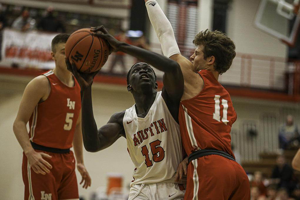 Austin sophomore Victor Idris (15) found his path to the basket blocked by Lakeville North's Jordan Wall (11) during the Packers' 55-50 victory. Photo by Mark Hvidsten, SportsEngine