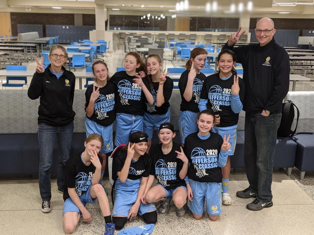 Mpls Lakers Youth Traveling Basketball Program Inc Girls 6th Grade Gold pose with their T-Shirts after placing 2nd at the Bloomington tournament in Bloomington, MN