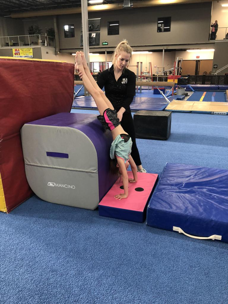 Coach spotting gymnast at skill clinic