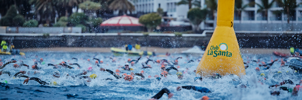 IRONMAN Lanzarote athletes swimming at Playa Grand in Puerto del Carmen as water is splashing around