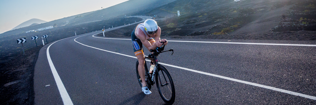 An IRONMAN 70.3 Lanzarote athlete biking at a winding street in the stark landscape of the southern part of the island