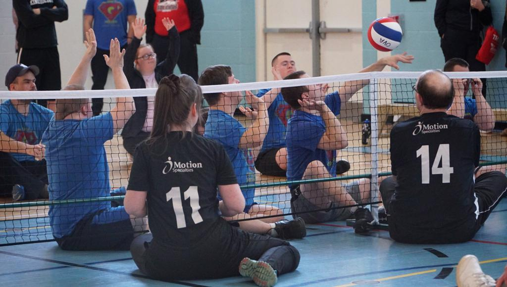 Players of different ages and abilities attacking the ball on a sitting volleyball net