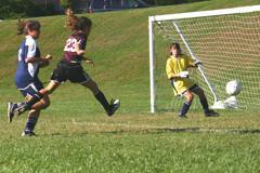 Girl Soccer Player kicking a goal