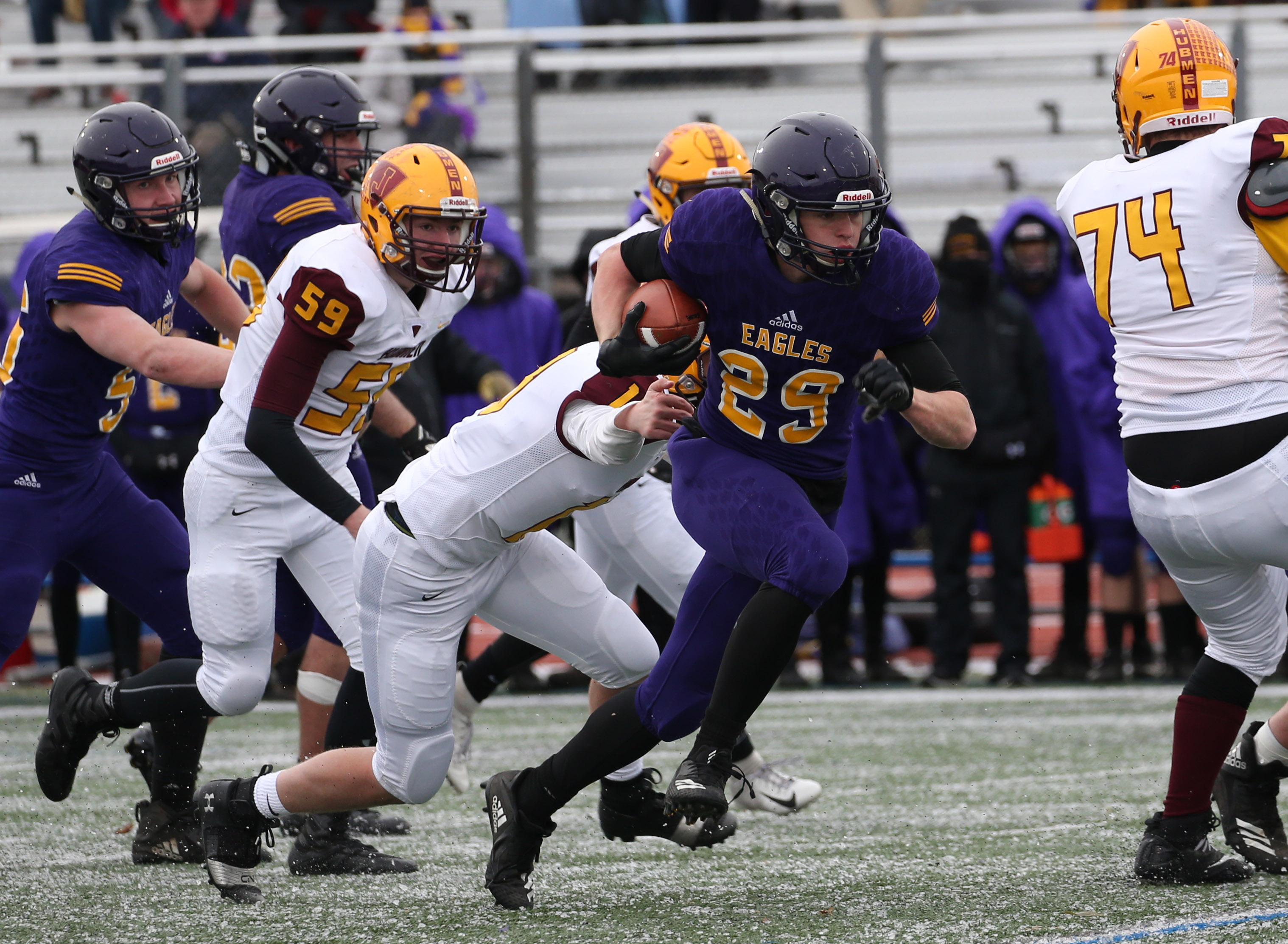 Zach Jungels (29) breaks free of the last tackle for a 33-yard touchdown in the fourth quarter solidifying a 24-0 win for Rochester Lourdes. Photo by Cheryl Myers, SportsEngine