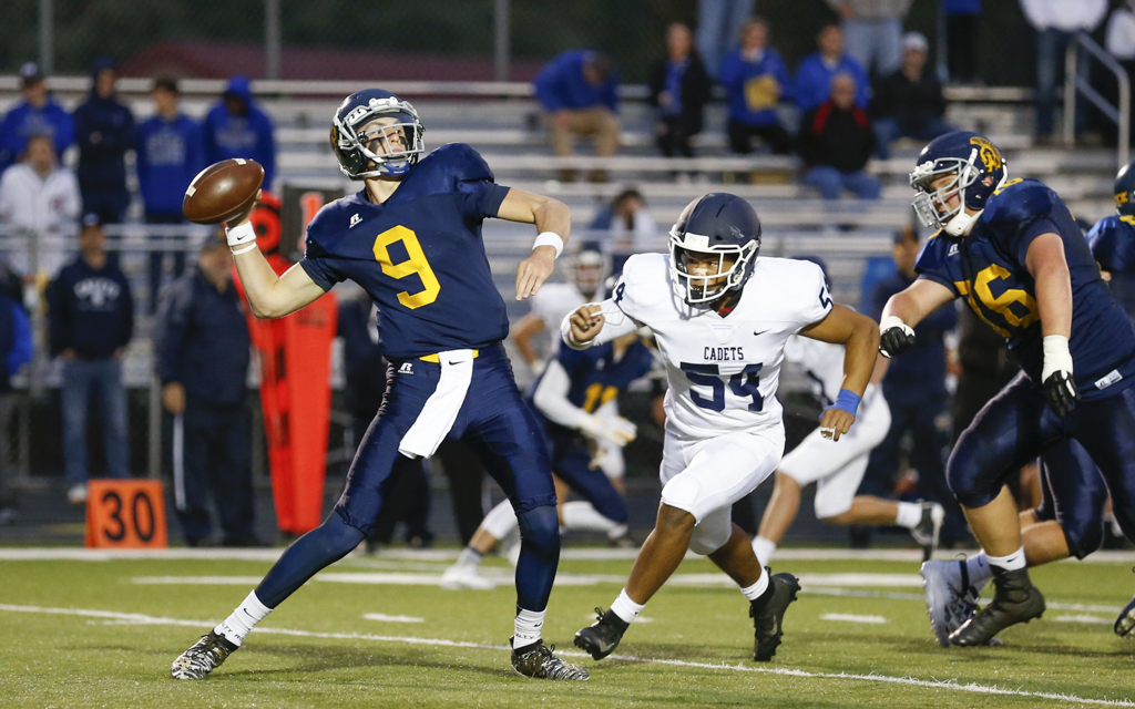 Mahtomedi's Johnathon Devore (9) drops back to pass as St. Thomas Academy's Garrison Solliday (54) applies pressure during the first half of Friday night's game. The  Zephyrs fell to the Cadets 38-0 at Mahtomedi HS. Photo by Jeff Lawler, SportsEngine