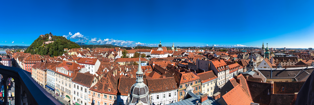 Fisheye photography of the Old Town of Graz with views of the Schlossberg and famous Clock Tower on a cloudfree and sunny day
