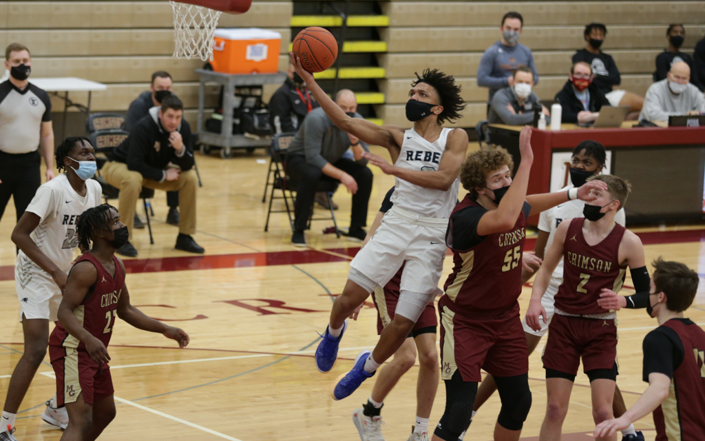 Champlin Park's Joshua Strong (with ball) drives to the basket during the first half of Friday's game against Maple Grove. Strong finished with 22 points in the Rebels' 57-50 victory over the Crimson. Photo by Jeff Lawler, SportsEngine to the basket durin
