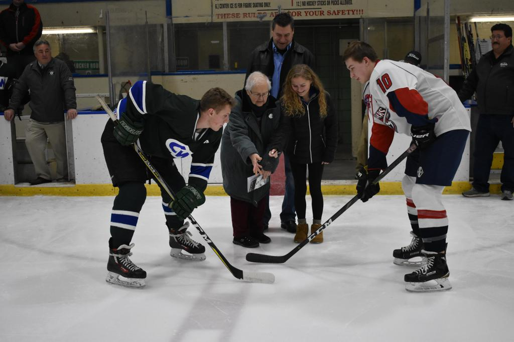 Celia Stone (L) and Hannah Stone (R), mother and daughter of Brian C. Stone, drop the puck on the first day of the high school hockey tourney named in his honor. They are joined by Scott Brady of tourney sponsor Brady-Sullivan Properties and players from