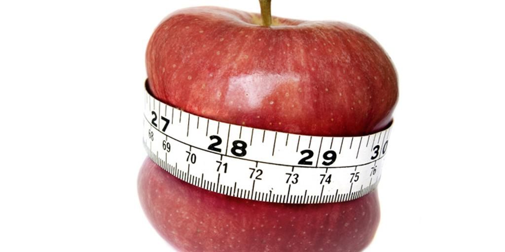 Red apple with tape measure around middle