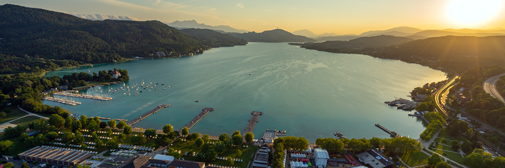 Bird's eye view of turquoise shimmering Lake Wörth, harbor, beaches, Pyramidenkogel and some cities in Klagenfurt, Carinthia
