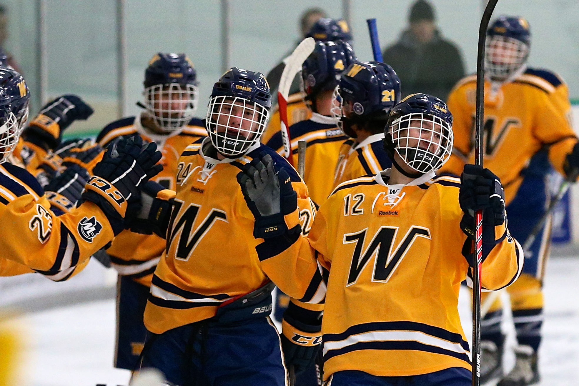 Nathan Dingmann (12) and Jake Moelk (24) lead the line of Trojans as they high five the bench players in Wayzata's 1-1 tie with Edina in the Turkey Trot Tournament at the Plymouth Ice Arena Nov. 22. Photo by Brian Nelson