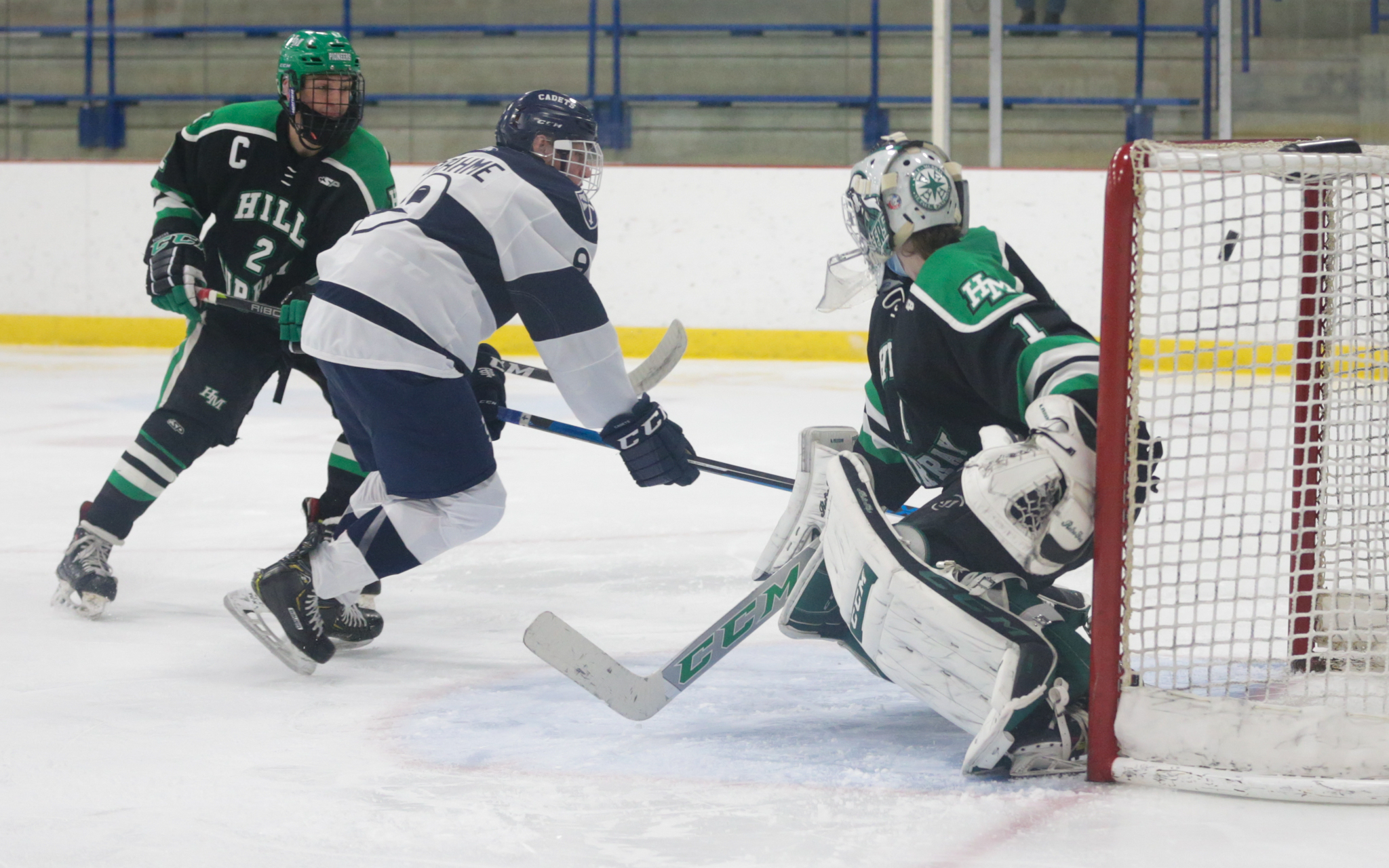 St. Thomas Academy's Tyler Grahme (9) flips a backhand past Hill-Murray goalie Nick Erickson (1) early in the first period Tuesday night. The Cadets fell at home to the Pioneers 7-3. Photo by Jeff Lawler, SportsEngine