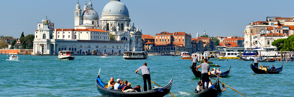 Gondoliers and other boats approaching the Basilica di Santa Maria della Salute and other majestic houses next to the Canal Grande in Venice
