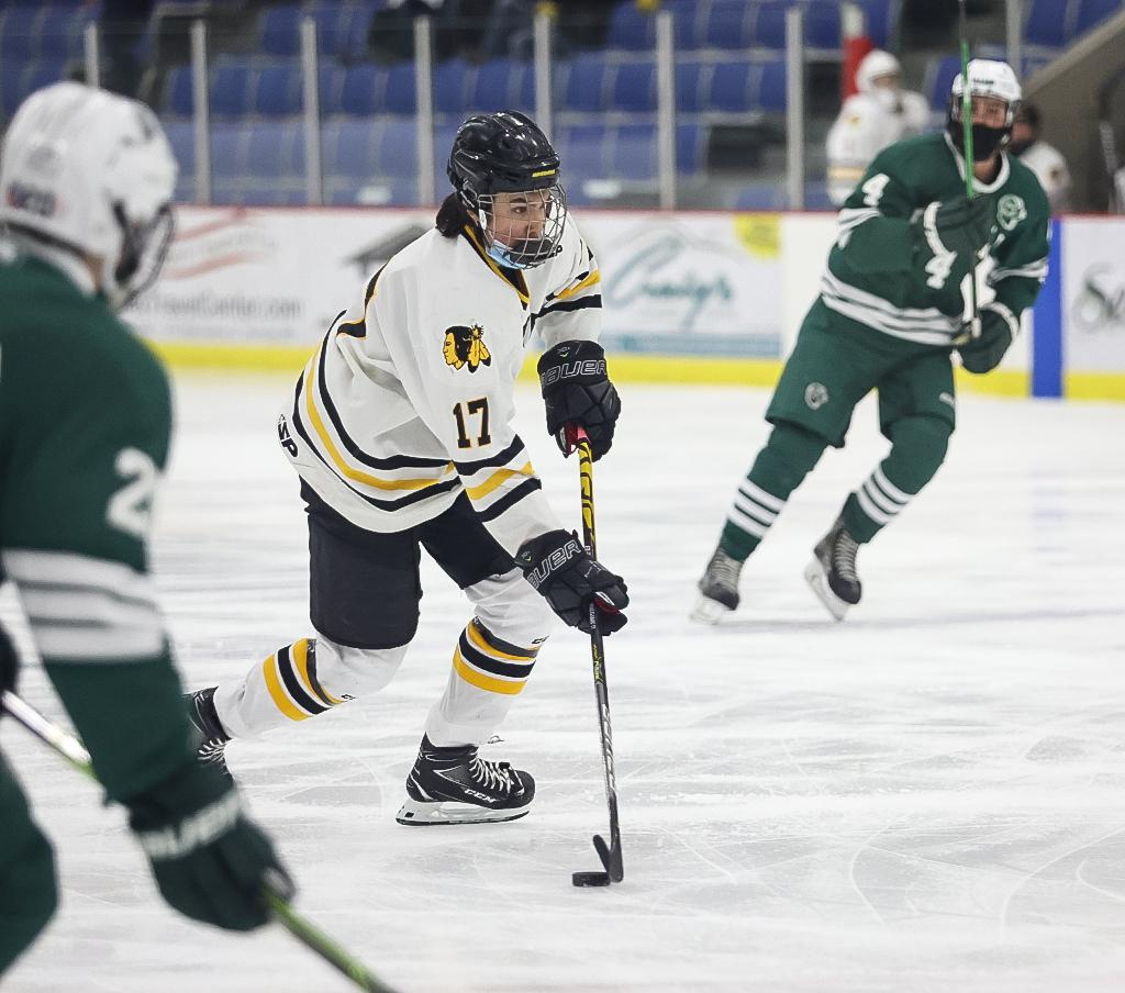 Sophomore forward Jayson Shaugabay (17) carries the puck through defenders in the neutral zone.  Shaugabay score two goals and added an assist in a 4-3 overtime loss to Roseau. Photo by Cheryl A. Myers, SportsEngine