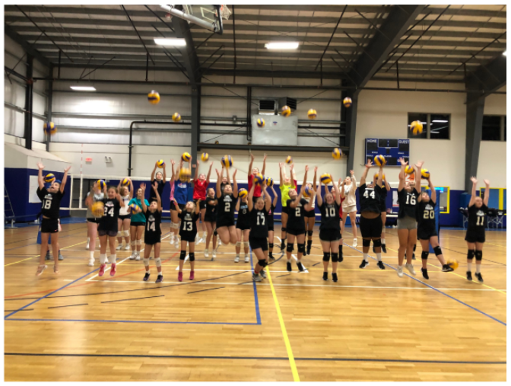 multiple volleyball players bouncing ball in gym