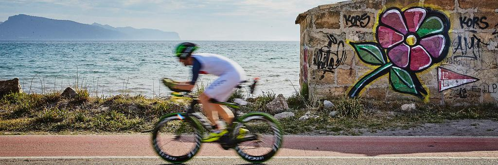 Athlete passing by the sea on the bike course at IRONMAN Mallorca