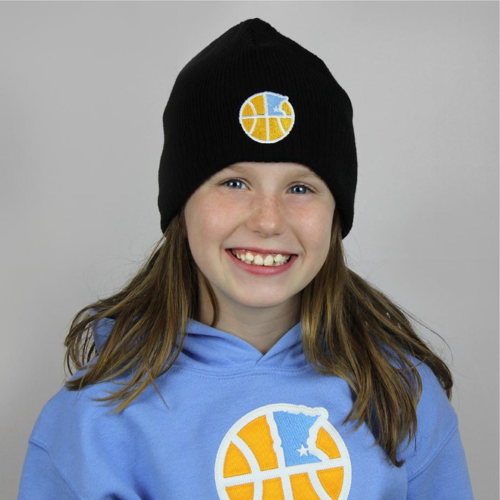 Young girl wearing black New Era beanie hat. Hat includes embroidered logo