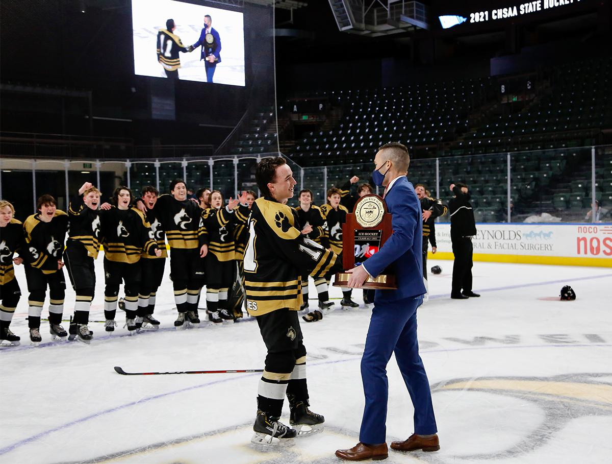 Battle Mountain captain Jensen Rawlings (11) accepts the CHSAA Class 4A state championship trophy on March 18, following the Huskies' 5-4 overtime defeat of Crested Butte in Loveland. Photo by Steven Robinson, SportsEngine