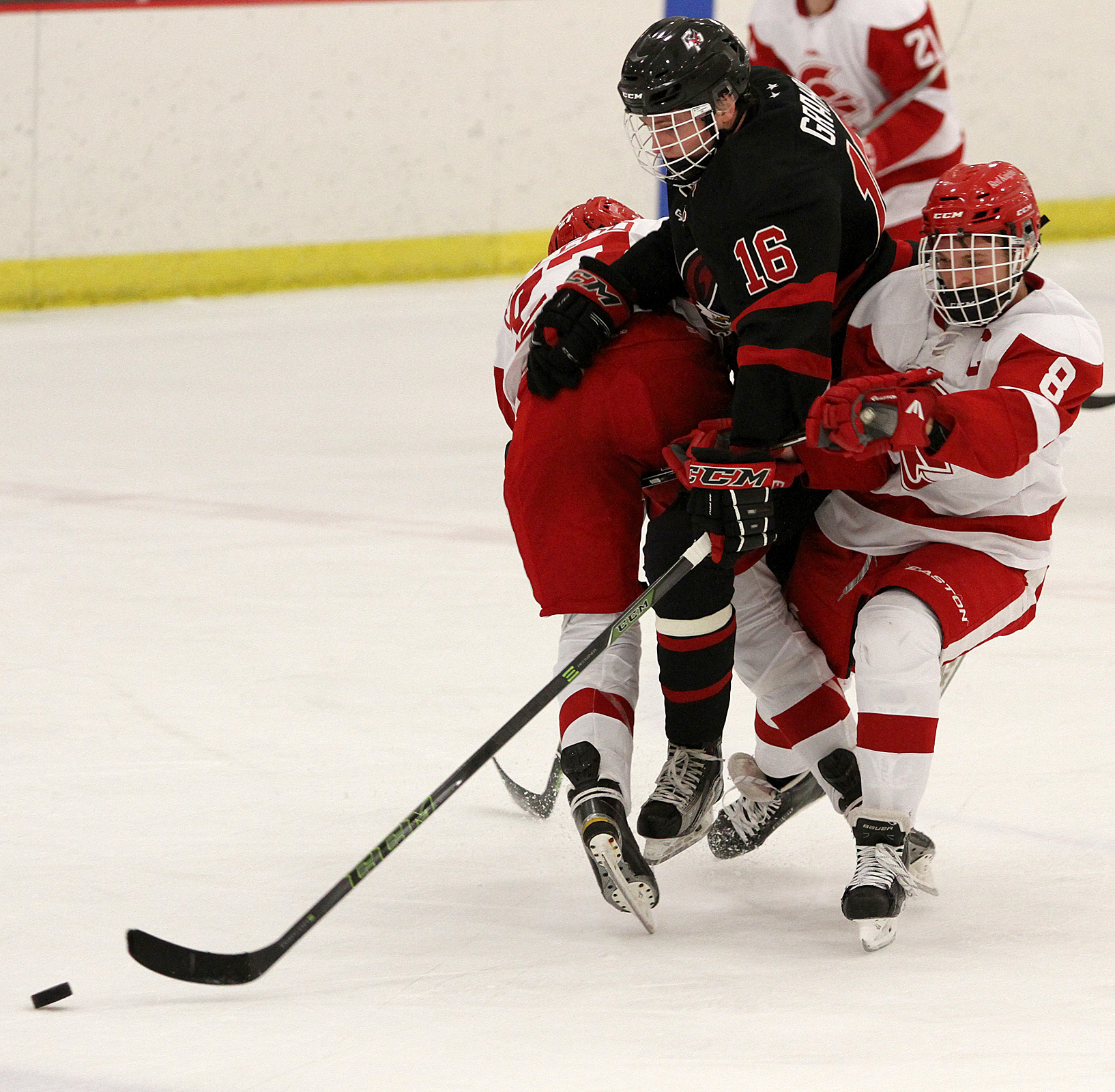 Eden Prairie senior Michael Graham is sandwiched by a pair of Benilde-St. Margaret skaters in the second period. Photo by Drew Herron