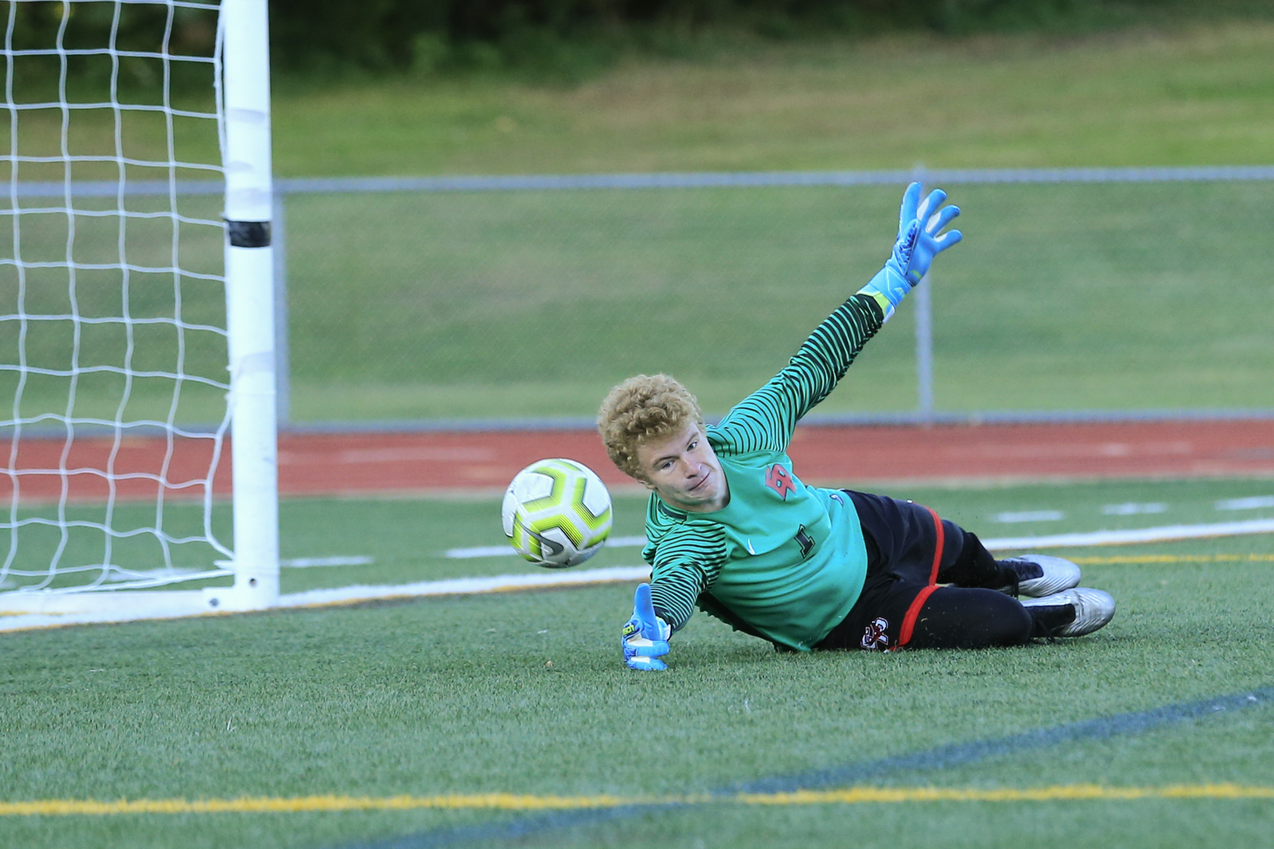 Eden Prairie goalkeeper Steven Mattison (1) dives to make a save in a Lake Conference tilt against Minnetonka Thursday evening. The Eagles fell to the Skippers 1-0 in Eden Prairie. Photo by Jeff Lawler, SportsEngine