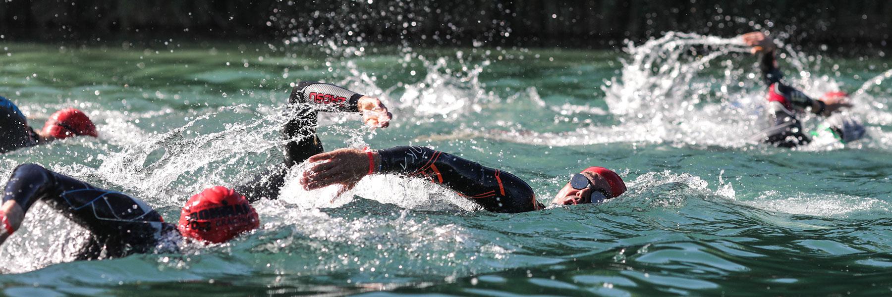 5150 Kraichgau athletes with red swim caps swimming in Hardtsee in Kraichgau