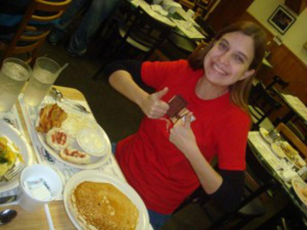 Meghan posing two thumbs up in front of bfast food