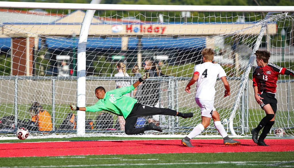 William Francis (4) slides the game-winning goal past goalkeeper Doug Habte (00). Duluth East heads home with a 2-1 overtime win over North St. Paul on Saturday afternoon. Photo by Cheryl Myers, SportsEngine