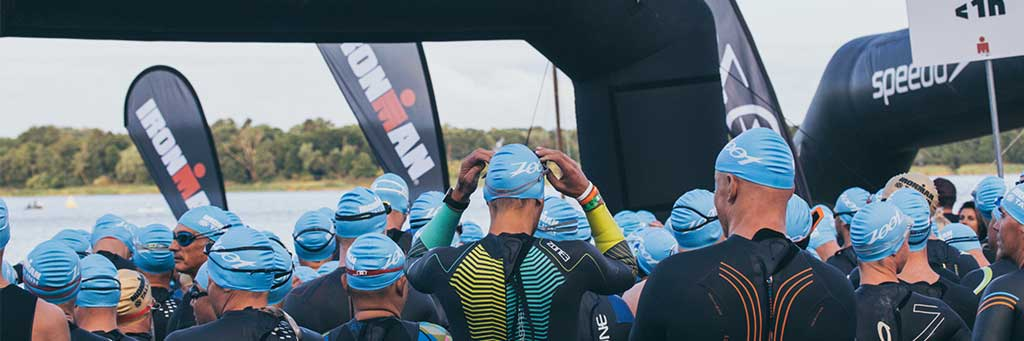 Athletes with blue swim caps standing next to each other and waiting to take on the swim course in lake Harku at IRONMAN 70.3 Tallinn