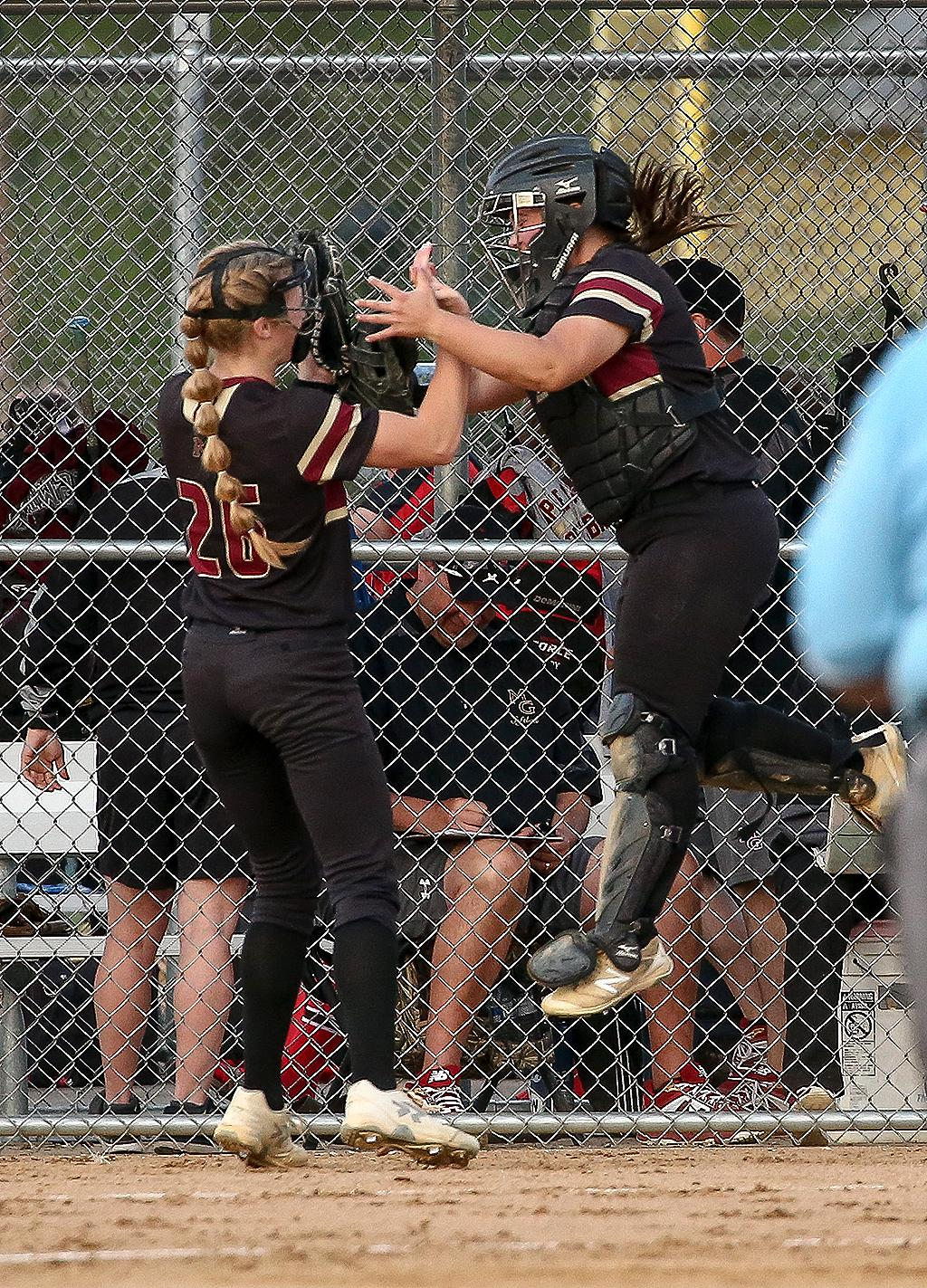 Pitcher Ava Dueck and catcher Sophie Culhane celebrate after shutting down Centennial's best scoring chance of the game. With the bases loaded, Dueck threw a pair of strikeouts to end the top of the first inning. Photo by Cheryl Myers, SporstEngine