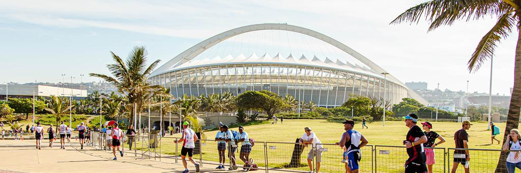 Athletes are running in the park along a palm tree avenue and passing by Moses Mabhida Stadium while supporters are watching and cheering on at IRONMAN 70.3 Durban