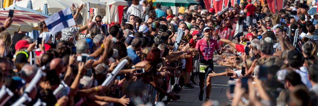 Athlete entering the Finish Line in Cervia with a massive crowd cheering him on at IRONMAN Italy Emilia-Romagna