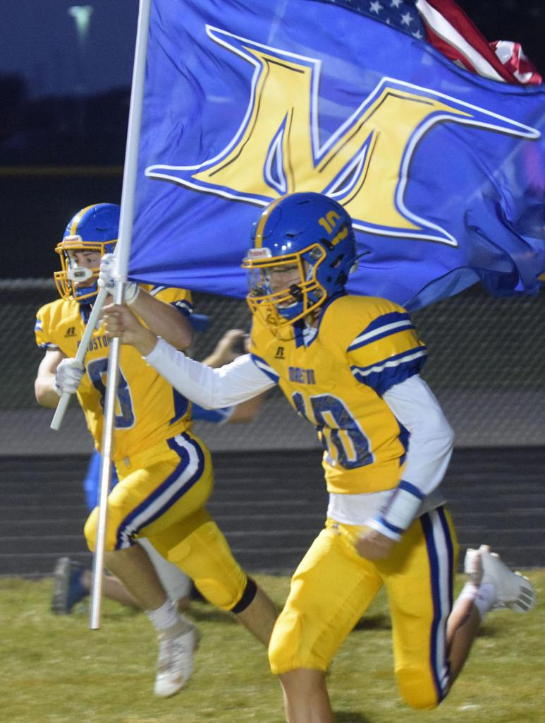 Spenser Lehman runs onto the field proudly carrying the Mauston Golden Eagle Flag.