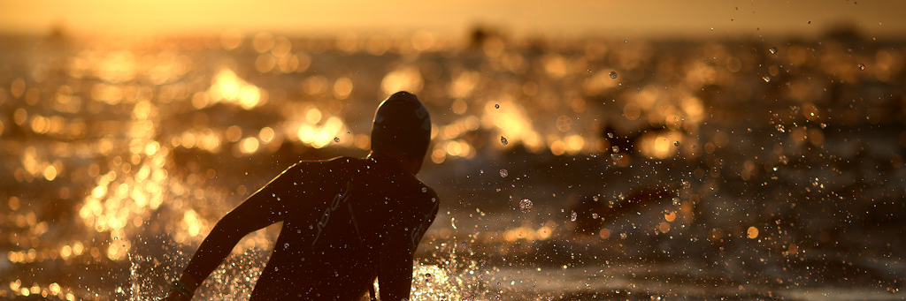 An IRONMAN 70.3 Weymouth athlete in Weymouth Bay at sunrise, where the sun's rays reflect golden on the water surface