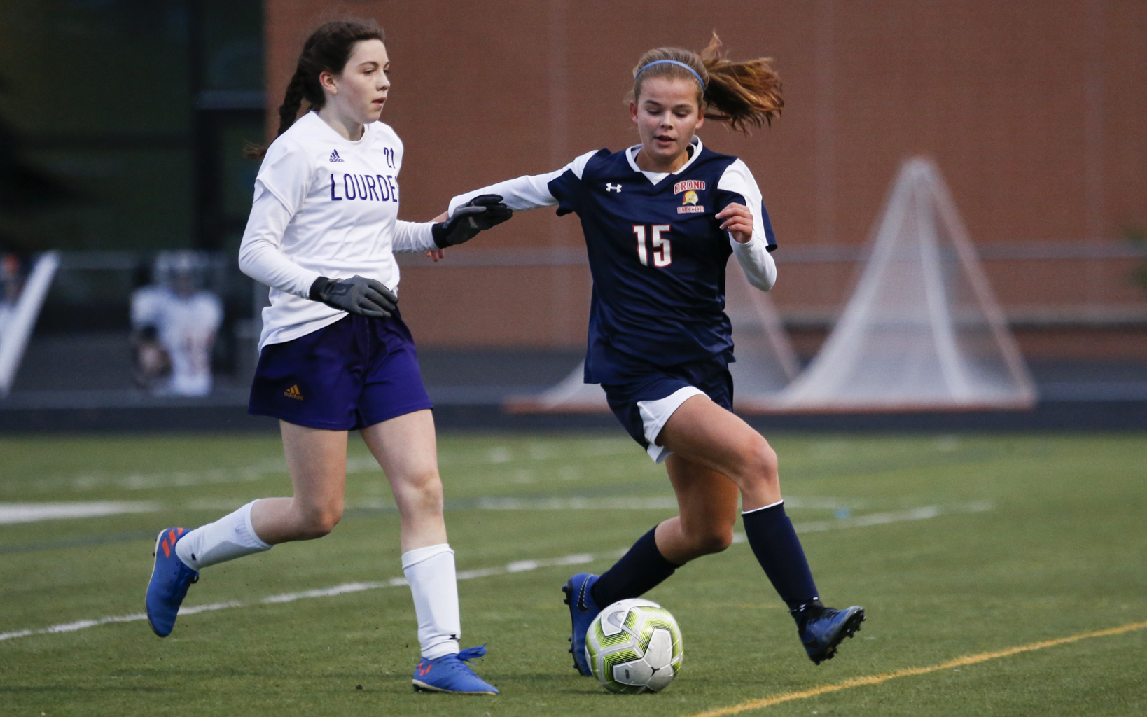 Orono's Nora Chouanard (15) races after a loose ball as Lourdes' Grace Buntrock (21) pursues. Chouanard's late first goal was the game winner in the Spartans a 1-0 victory over the Eagles. Photo by Jeff Lawler, SportsEngine