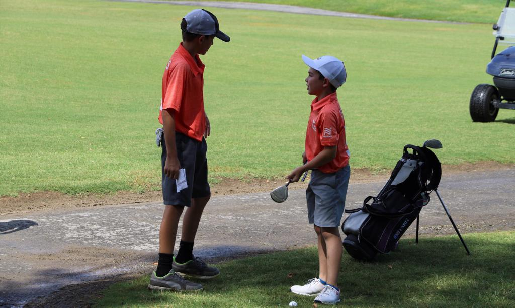 PGA Jr. League player talks with teammate