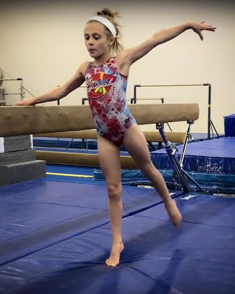 Gymnast practicing form and balance using beam
