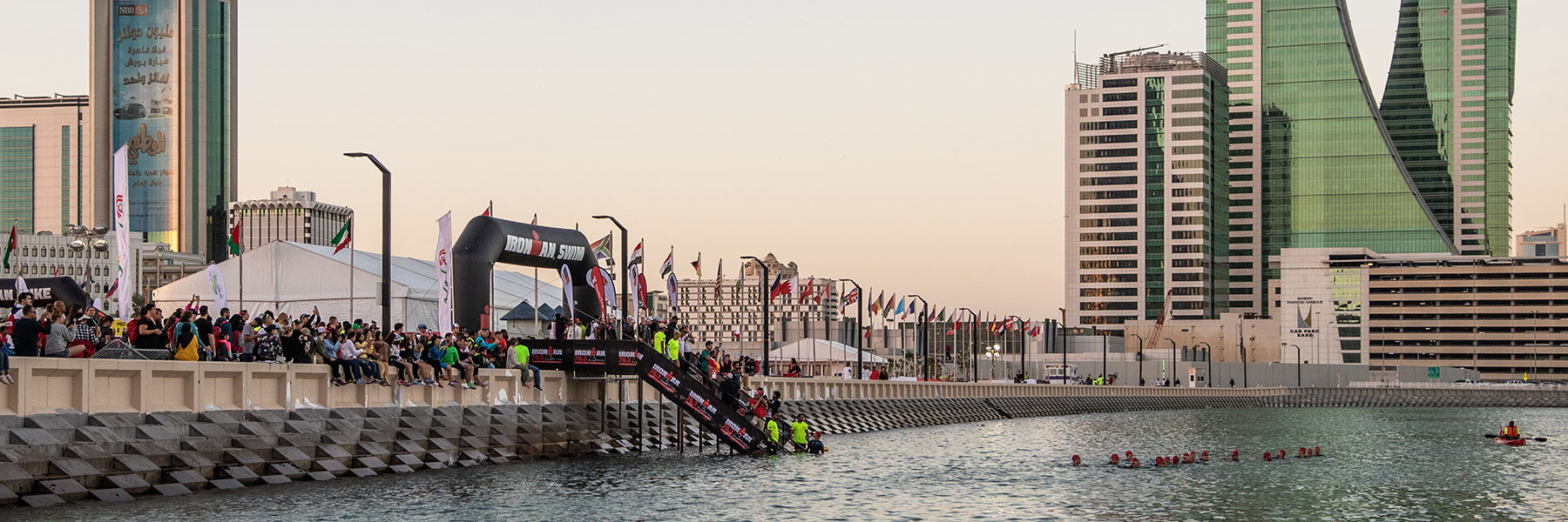 """IRONMAN 70.3 Bahrain athletes are in the water in front of """"The Avenues"""" in Manama and wait for the signal of the swim start, while people are watching"""